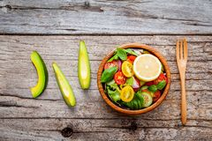 The bowl of healthy vegan salad . Various vegetables avocado, to. Mato, cucumber, red cabbage, basil and onion on shabby wooden background royalty free stock images