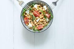 A bowl of healthy vegetarian salad with chickpeas, two forks on white wooden background, top view,copy space stock image