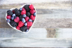 Bowl of Heart Healthy Berries. Healthy fresh fruit salad with strawberries, blackberries, blueberries and raspberries. in heart shape bowl Royalty Free Stock Photography