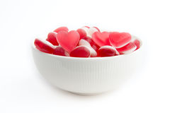 Bowl of Heart Shaped Sweets. A white bowl full of heart shaped red and white sweets stock photography