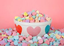 Valentine candy hearts in and around holiday bowl pink background. Bowl with hearts holding pile of candy hearts surrounded by pile of more candy on pink royalty free stock photo