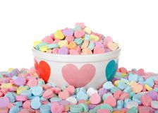 Valentine candy hearts in and around holiday bowl isolated. Bowl with hearts holding pile of candy hearts surrounded by pile of more candy isolated on white royalty free stock photography