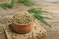 Bowl of hemp seeds on table. Bowl of hemp seeds on wooden table stock photography