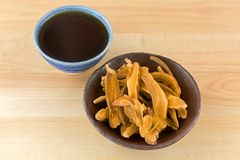 Bowl of herbal sliced dried Lingzhi mushroom next to hot Reishi Stock Photo