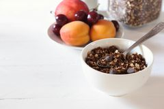 Bowl of chocolate granola on a white table royalty free stock photos