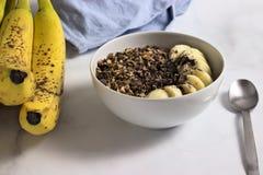 Bowl of homemade granola with banana, cocoa and carob stock photo
