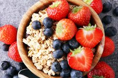 Bowl of homemade granola with  fresh berries on grey background Stock Images