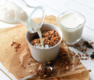 A bowl of homemade granola, a glass of yoghurt and a bottle of milk stock photos