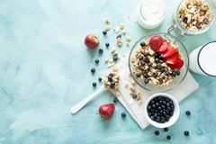 Bowl of homemade granola with strawberry, blueberry, milk and yo. Gurt on turquoise wooden background. Top view. Flat lay. Copy space Stock Photos