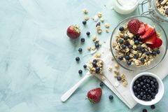 Bowl of homemade granola with strawberry, blueberry, milk and yogurt on turquoise wooden background. Top view. Flat lay. Copy space royalty free stock images