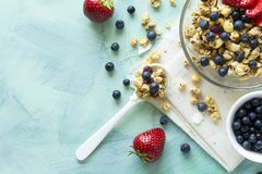 Bowl of homemade granola with strawberry, blueberry, milk and yogurt on turquoise wooden background. Top view. Flat lay. Copy space royalty free stock photography