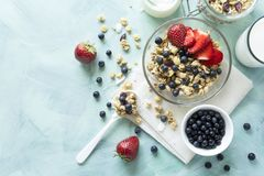 Bowl of homemade granola with strawberry, blueberry, milk and yogurt on turquoise wooden background. Top view. Flat lay. Copy spac. E stock images