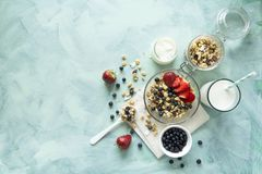 Bowl of homemade granola with strawberry, blueberry, milk and yogurt on turquoise wooden background. Top view. Flat lay. Copy spac. E stock photography