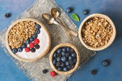 Bowl of homemade granola with yogurt and fresh berries blueberries and raspberries on blue rustic background. Healthy diet. Breakfast. Overhead, top view, flat royalty free stock images