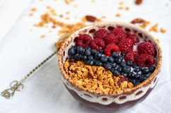 Bowl of homemade granola with yogurt, fresh berries and spoon Stock Photos