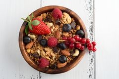 Bowl of homemade granola with yogurt and fresh berries on wooden royalty free stock images
