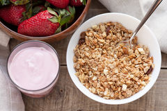 A bowl of homemade granola with yogurt and fresh strawberries on a wooden background. Healthy breakfast stock images