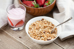 A bowl of homemade granola with yogurt and fresh strawberries on a wooden background. Healthy breakfast stock photography