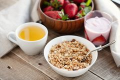 A bowl of homemade granola with yogurt and fresh strawberries on a wooden background. Healthy breakfast with green tea royalty free stock photos