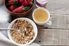 A bowl of homemade granola with yogurt and fresh strawberries on a wooden background. Healthy breakfast with green tea stock photos