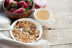 A bowl of homemade granola with yogurt and fresh strawberries on a wooden background. Healthy breakfast with green tea stock photo