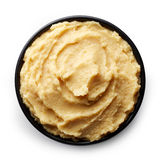 Bowl of homemade hummus. Black bowl of homemade hummus  on white background from top view Stock Image
