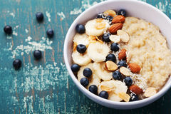 Bowl of homemade oatmeal porridge with banana, blueberries, almonds, coconut and caramel sauce on teal rustic table from above royalty free stock image