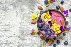 Bowl of homemade smoothie topped with fresh blueberries, nuts, chia and pumpkin seeds and flowers. Over white wooden background. top view. healthy breakfast Royalty Free Stock Images