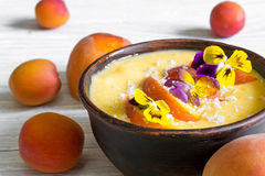 Bowl of homemade yellow smoothie with fresh mango, peaches and apricots topped with coconut and flowers Stock Photos