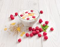 Bowl of homemade yogurt with muesli and fresh raspberry. On wooden table. Fresh yogurt. Healthy food concept. High resolution product Stock Image