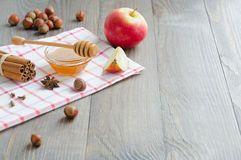 Bowl of honey, honey stick, cinnamon, hazelnuts and red apple Stock Photography