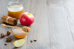 Bowl of honey, honey stick, cinnamon, hazelnuts and red apple Royalty Free Stock Photo