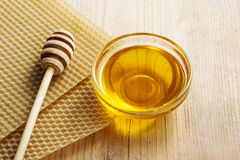 Bowl of honey and honeycomb in the background. Stock Images