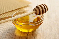 Bowl of honey and honeycomb in the background. royalty free stock image