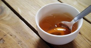 Bowl of honey with spoon 4k. Bowl of honey with spoon on a wooden table 4k stock video footage