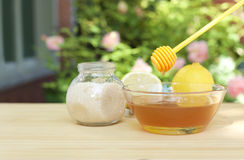 Bowl of honey and sugar and lemons on wooden table Stock Images