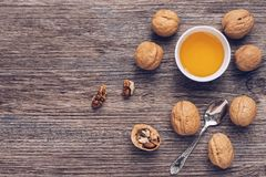 A bowl of honey and walnuts on a wooden brown table. View from above. A bowl of honey and walnuts on a wooden brown table. View from above Stock Photos