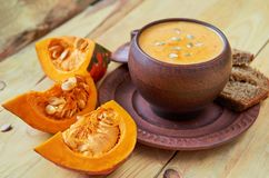 Bowl of hot pumpkin soup with sliced yellow pumpkins and seeds on the wooden background. Traditional autumn or thanksgiving dish. Bowl of hot pumpkin soup with royalty free stock photos