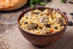 Bowl of hot traditional Arabic national rice food. Called pilaf with fried meat, onion, carrot and garlic. Served in rustic clay plate on vintage kitchen table Royalty Free Stock Images