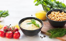 Bowl with hummus, chickpeas, lemon, cherry tomatoes and herbs on a white rustic wooden background. Middle Eastern cuisine. Backgro royalty free stock photos