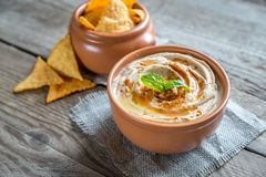 A bowl of hummus with corn chips. On the wooden table Royalty Free Stock Photo