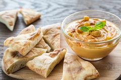 A bowl of hummus with pita slices Stock Photo