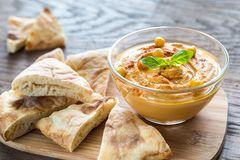 A bowl of hummus with pita slices Stock Images