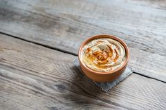 A bowl of hummus. On the wooden table stock image