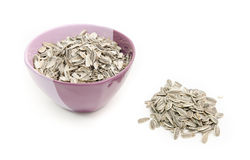 A bowl with husks and sunflower seeds next to it on a white background Stock Photo