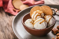 Bowl of ice cream with caramel sauce and cookies. On table stock images