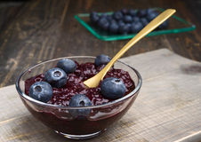 Bowl with jam and blueberries, on wood Stock Image