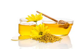 The bowl and the jar of honey near a pile of pollen and flower Royalty Free Stock Photo