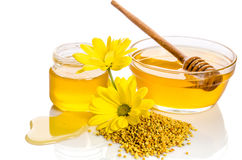 Bowl and the jar of honey near a pile of pollen and flower Stock Image