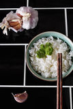 Bowl of jasmine rice chopsticks and garlic. On tiled background Stock Photos